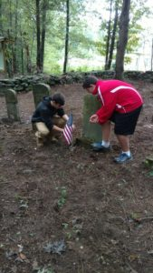 Scouts putting flag on grave of Christopher Wilbur